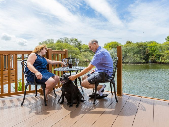 A couple and their dog sat on the decking of their home on Willowgrove